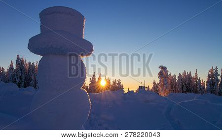 Snowman Looking At Beautiful Winter Landscape And Setting Sun In Forest. Winter Scape Tranquility Im
