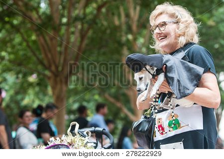 Atlanta, Ga - August 18:  A Woman Carries A Small Dog Dressed Like Darth Vader From Star Wars As She