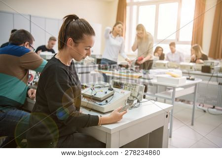 Group of young students doing technical vocational practice with teacher in the electronic classroom, Education and technology concept