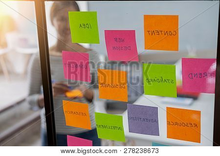 Web Designer Brainstorming For A Strategy Plan. Colorful Sticky Notes With Things To Do On Office Bo