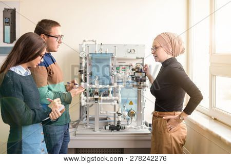 Group of students doing technical vocational practice with young female muslim teacher in the electronic classroom, Education and technology concept