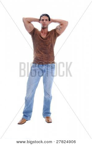 Muscular young man standing in jeans and a brown V neck tee shirt with his arms raised and hands behind his head