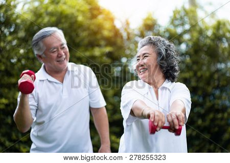 Asian Senior Couple Exercising With Red Dumbbells At The Outdoor Park Togetherness. Smiling Chinese