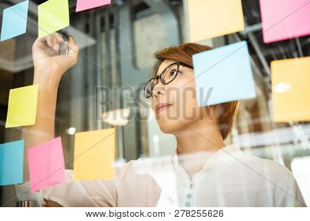 Young Woman Designer Writing New Ideas At Sticky Notes On Glass Wall. Brainstorming Concept.