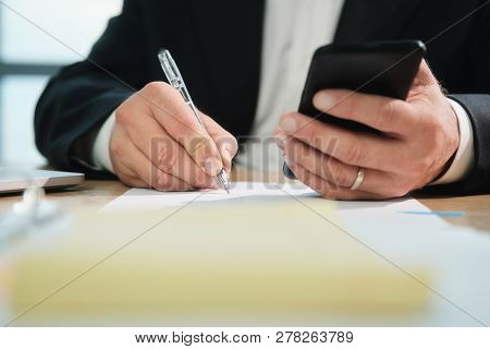 Hands Of Business Man Writing With Pen And Holding Phone