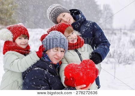 A Mother With Her Daughters Twins And Her Son Dressed In Warm Colorful Clothes Are Playing Outdoors