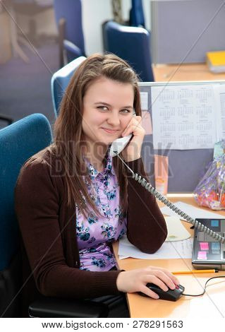 Cheerful Young Beautiful Woman Talking On The Phone And Looking At Camera With Smile While Sitting A