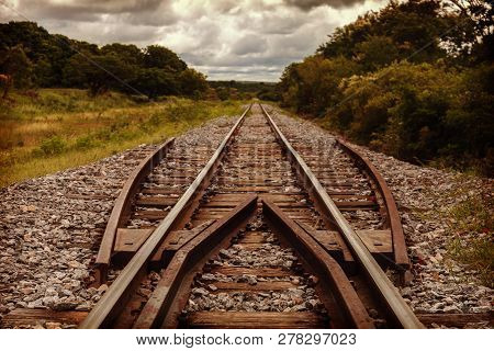 Railroad Tracks In The Middle Of Wildlife. Dramatic Sky With Clouds. Horizontal Layout