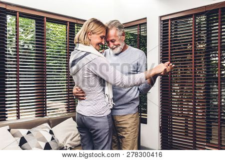 Happy Smiling Romantic Senior Couple Dancing Together While Feeling Relaxed In Living Room At Home.r