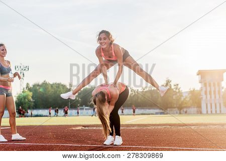 Fit Women At The Stadium Playing Leap Frog.