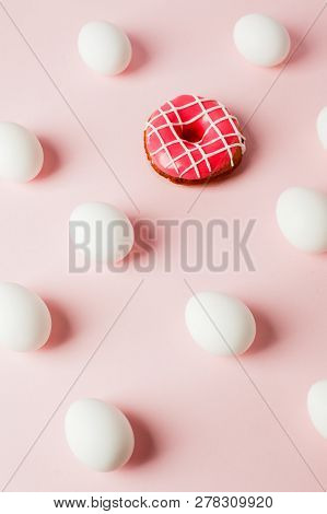 Easter white eggs repetition with shadow and pink donut on pink pastel background, system error, copy space, trendy background poster