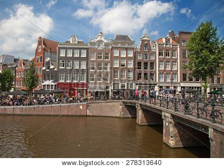 AMSTERDAM - JULY 10: Canals of the Amsterdam city on July 10, 2016 in Amsterdam, Netherlands. The historical canals of the city surrounded by traditional dutch houses is main attractions of Amsterdam.