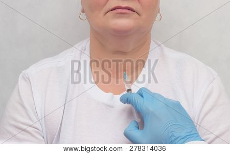 Doctor makes a patient patient a thyroid biopsy on suspicion of oncology, thyroid node, close-up, medic, endocrinology poster