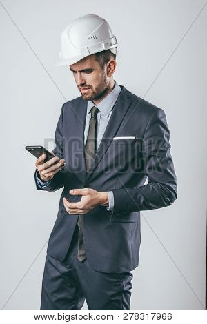 Engineer In Hardhat And Suit Browsing Smartphone With Displeased Face Expression While Standing On L