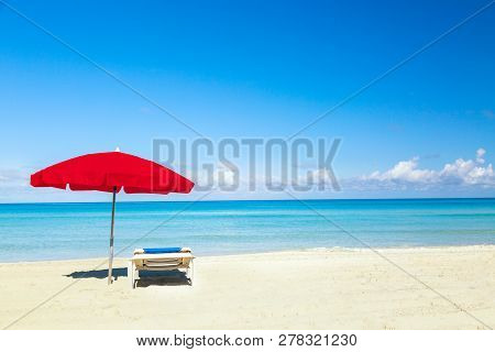 A Sun Lounger Under Red Umbrella On The Sandy Beach By The Sea And Sky. Vacation Background. Idyllic
