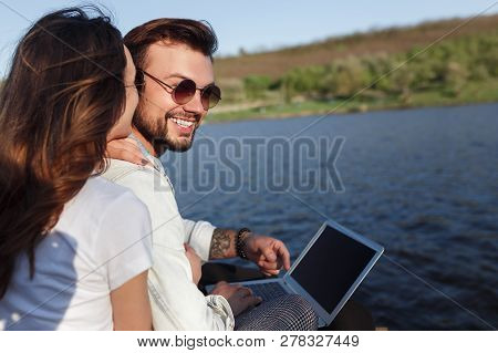 Young Man And Woman Smiling And Browsing Modern Laptop While Sitting Near Calm Lake On Sunny Day
