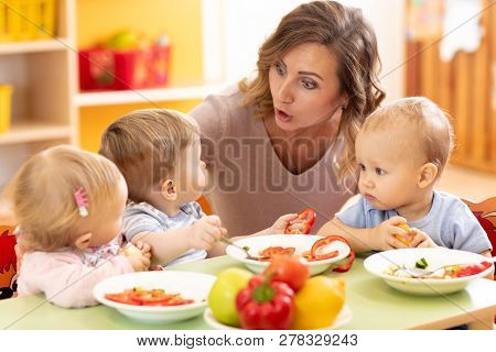 Cute Little Children Eating Healthy Food At Daycare Centre