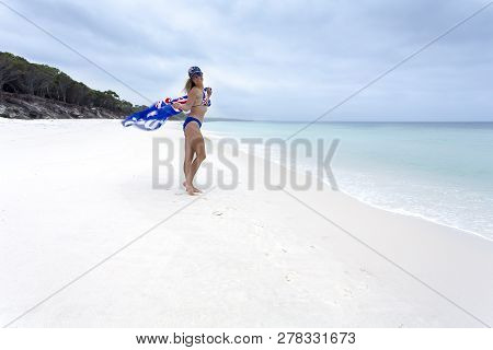 Australian Girl Holding An Australian Flag Flapping In The Wind. She Also Wears Bikini With Australi
