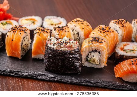 Asian Traditional Cuisine. A Large Set Of Rolls And Sushi On A Black Slate Stone, On A Wooden Table