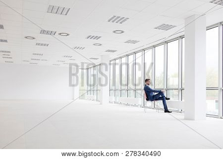 Full length of thoughtful young businessman sitting on chair while looking through window at new empty office