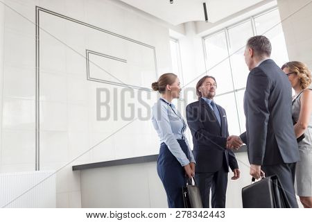Businessmen greeting while standing with colleagues at reception lobby in office