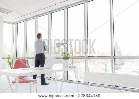 Full length of thoughtful mature businessman looking through window at new office