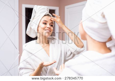 Portrait Of Beautiful Young Woman Wearing Bathrobe Applying Face Cream While Looking In Mirror After