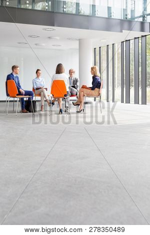 Business people planning strategy while sitting on chairs during meeting