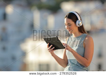 Relaxed Woman Browsing Tablet Videos In A Town At Sunset