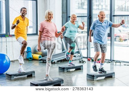 Smiling Multiethnic Senior Athletes Synchronous Exercising On Step Platforms At Gym