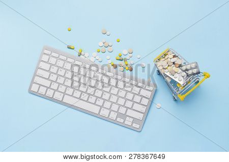 Keyboard And Cart With Pills On A Blue Background. Concept Of Buying Drugs Online, Ordering Drugs On