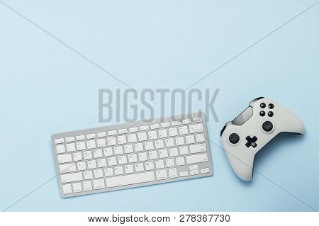 Keyboard And Gamepad On A Blue Background. The Concept Of Computer Games, Entertainment, Gaming, Lei