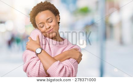 Beautiful young african american woman over isolated background Hugging oneself happy and positive, smiling confident. Self love and self care