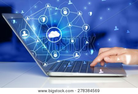 Hand using laptop with centralized cloud computing system and network security concept