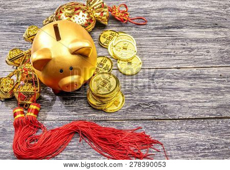Piggy Bank With Golden Coins And Chinese Ornament On The Wooden Table. Chinese New Year. Year Of The