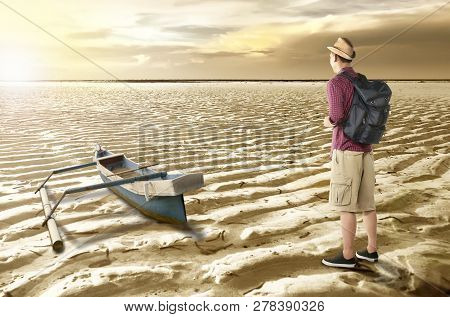 Rear View Of Asian Traveler Looking At Drying Water On The Lake. Climate Change Concept