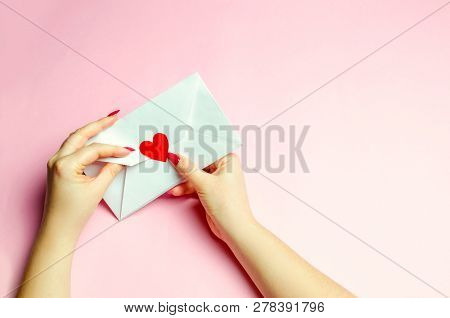 Female hand opens envelope with a red heart. A love letter to the beloved. Valentines day concept. Greeting valentine card. Declaration of love. Wedding invitation. View from above. Flat lay poster