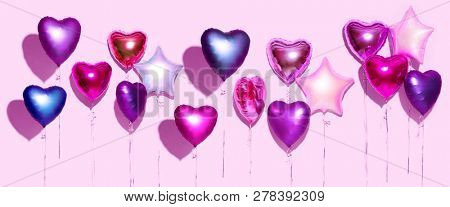 Air Balloons. Bunch of colorful purple, pink, blue heart shaped foil balloons on pink background. Love. Holiday celebration. Valentine's Day party decoration. Birthday. Metallic balloon. Wide screen