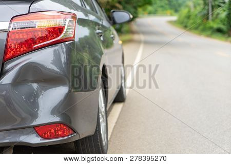 Back Of Gray Car Get Damaged From Accident On The Road. Vehicle Bumper Dent Broken By Car Crash. Roa