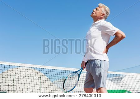 Mature man grimacing with backache while holding tennis racket against clear blue sky on sunny day