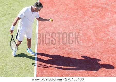 High angle view of confident mature man serving on tennis court during match on sunny day