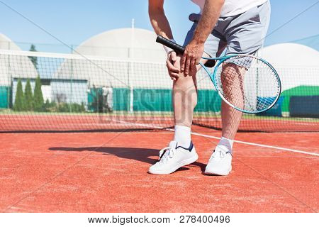 Low section of mature man holding tennis racket while suffering from knee pain on red tennis court during summer
