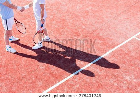 Low section of mature men shaking hands while standing on tennis court during match