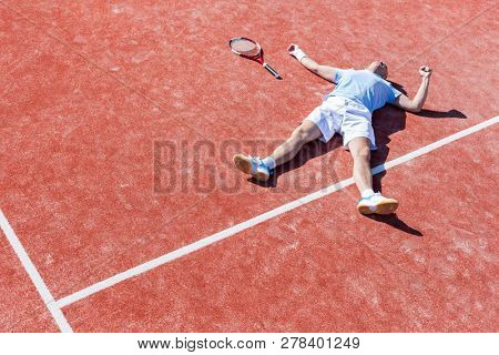 Full length of disappointed mature man lying by tennis racket on court during summer