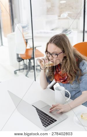 Businesswoman using touchpad of laptop while having breakfast in office