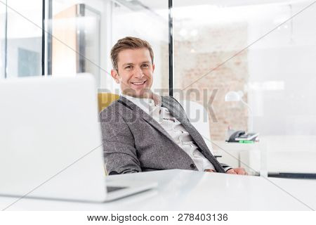 Portrait of businessman smiling while sitting at desk