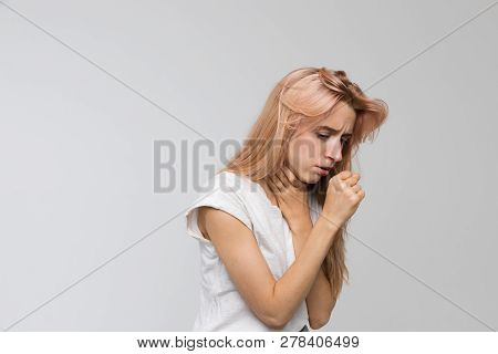 Studio Portrait Of Young Unhealthy Coughing Woman Feeling The First Symptoms Of Illness/suffers From