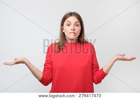 Young Woman With Widely Opened Eyes Having Hesitation Shrugging Her Shoulders