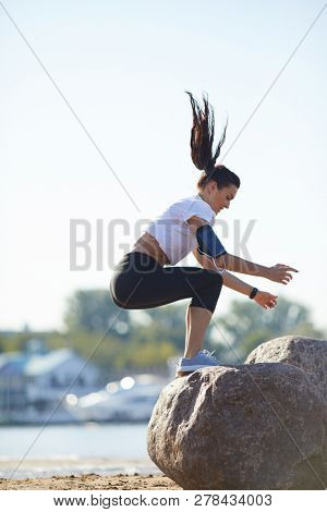 Workout on beach: attractive athletic young woman with smartphone armband jumping on stone while doing jump squat on coastline poster