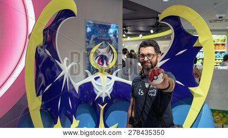 Tokyo, Japan - August 2018: Happy Tourist Posing Infront Of A Pokemon Figure At Pokemon Center Store